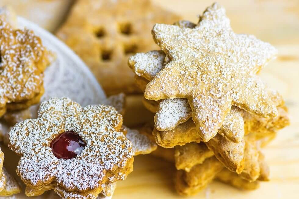 Linzer Cookies - Linzer tarts are made of an  almond dough with a sweet jelly filling inside, and they are definitely a  holiday favorite. These cookies originated in the town of Linz in Austria  many years ago, where they were called Linzertorte. A traditional  Linzetorte is comprised of a buttery dough made of almonds, lemon zest,  and cinnamon, and filled with black currant preserves. In America,  raspberry replaced the black currants, which is how many of us eat them.  Linzertortes have been a traditional European Christmas cookie  since about 1653, when they were made by baker Johann Konad Vogel in  Austria.  They are a little time-consuming to make, but well worth it.