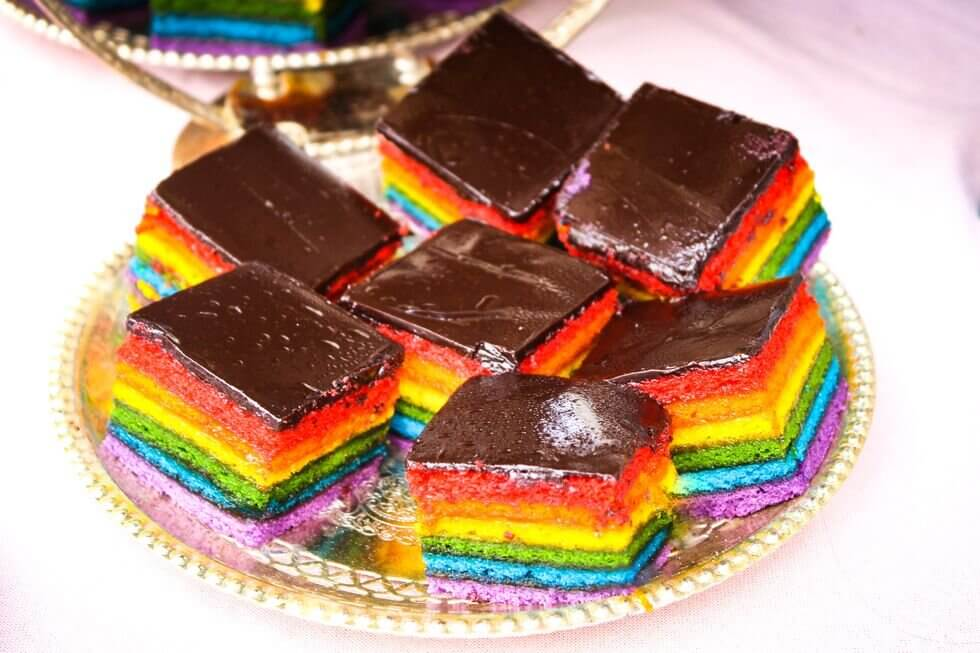Italian Rainbow Cookies - Rainbow cookies might not technically qualify as cookies (they're basically layers of sponge cake with chocolate frosting and a jelly filling), but they're delicious, and a lasting tradition this time of year. They are typically made of three layers of red, green, and white sponge cake. According to Italian Sons and Daughters of America, many people believe that rainbow cookies are an Italian-American recipe, something created to honor the Italian flag by Italian-American bakers. This doesn't seem out of the realm of possibility, however, the site also points out that some people have spotted rainbow cookies in Italy around Christmastime, suggesting that maybe they're more authentic than most people believe.